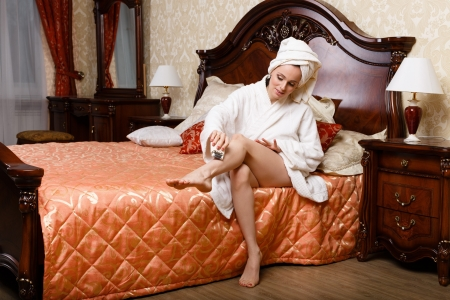 Beautiful young woman shaving her legs in bedroom. Concept of body care.