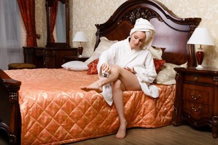 美しい若い女性の寝室で彼女の足を剃るします。ボディ ・ ケアの概念。