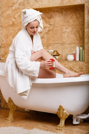 Young woman with a massager in a bathroom. Concept  of body care. Stock Photo - 19356377