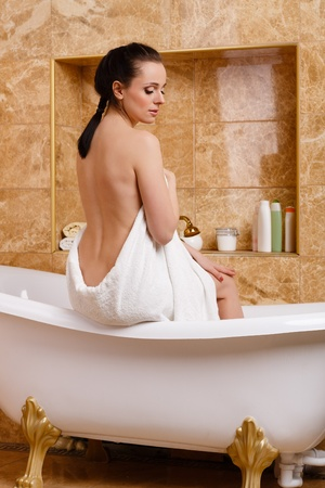 Young woman wiping body by a towel in house  bathroom. Concept  of body care. photo