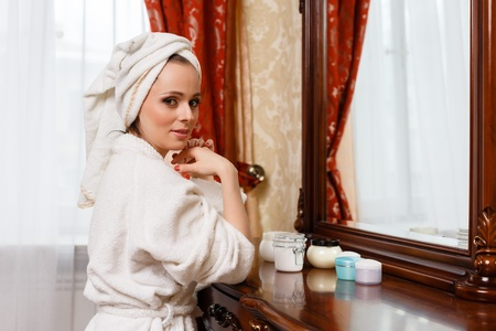 Young woman with cosmetic cream sits before a house  dressing table. Concept body care. photo