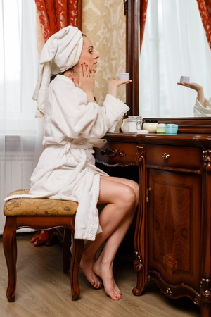 Young woman with cosmetic cream sits before a house  dressing table.Concept body care. Stock Photo - 19356362