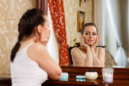 Young woman with cosmetic cream sits before a house  dressing table.