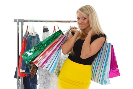Beautiful female shopper with shopping bags and clothes on hangers on a white background. photo