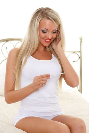 Happy young woman checking pregnancy test sits on a bed in the room. Positive result. photo