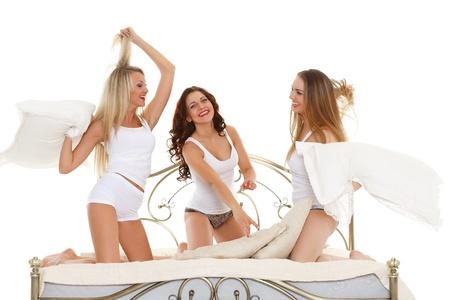 chicas divirtiendose: Chicas alegres felices en divertirse sentado en la cama sobre un fondo blanco. Fiesta pijama.