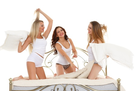 white pillow: Happy cheerful girls having fun sitting on the bed on a white background. Pyjamas party.