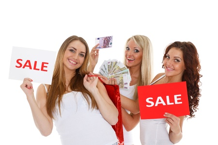 Three beautiful cheerful  girlfriends with sale sign, purchases and money stand on a white background photo