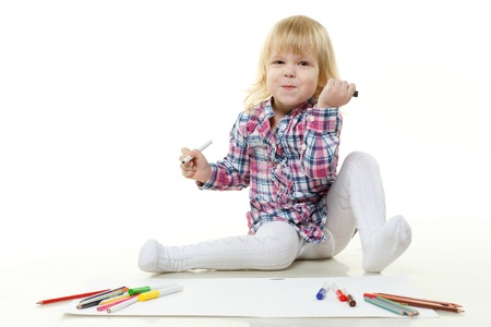 Happy little girl draws a picture on a white background. photo