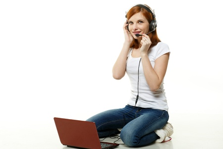 Pretty young red-haired woman in headset with a laptop sits on a white background. photo