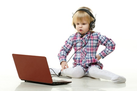 The little pretty girl in headset with laptop sits on a white background. photo