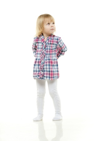 cagey: The little girl hides hands behind the back and looks upwards on a white background. Stock Photo