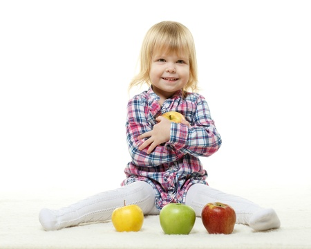 Sweet small girl with fresh apples on a white background. Healthy food. photo