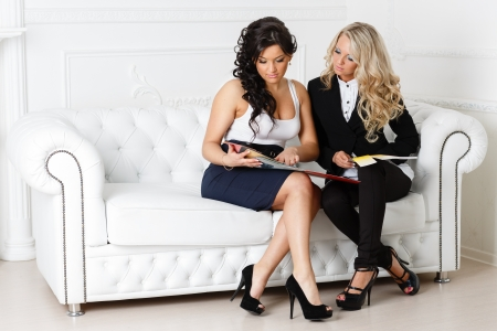 decorator: Young female designer of interior with client sit on the sofa at the office. Stock Photo