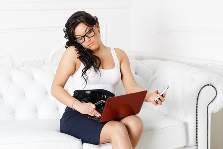 overworking: Stressed  young businesswoman with phones and laptop sits on a white sofa. Stock Photo