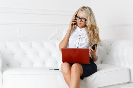 Stressed  young businesswoman with phones and laptop sits on a white sofa. photo
