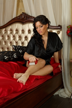 Young woman with a massager in a bedroom. Concept  of body care. Stock Photo - 19808976