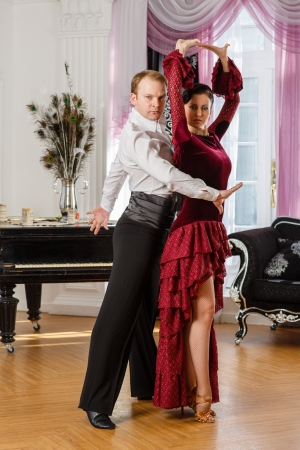 Dancing young couple in the room. photo