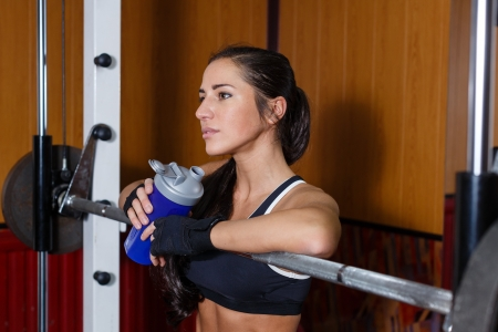 The sports young woman with a protein cocktail in a shaker stands in a gym.