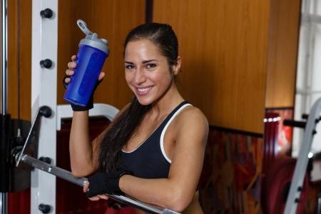 De sportieve jonge vrouw met een eiwit cocktail in een shaker staat in een sportschool. Sportvoeding.