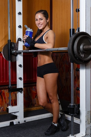 The sports young woman with a protein cocktail in a shaker stands in a gym. Sports nutrition. photo