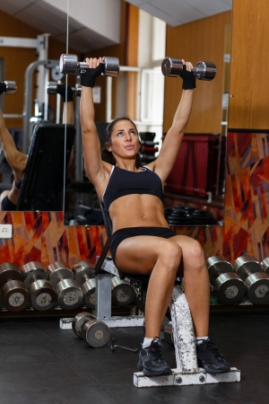 Young sports woman doing exercises with dumbbells in the gym. Fitness. photo