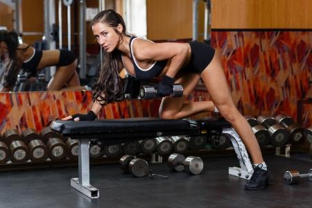 Young sport vrouw doen oefeningen met halters in de sportschool. Fitness.