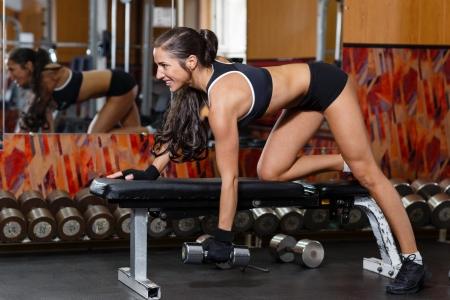 pesas: Mujer deportiva joven que hace ejercicios con pesas en el gimnasio. Fitness.