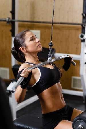 Sports young woman doing exercises in the gym on Lat Machine.