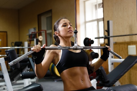 Sports young woman doing exercises in the gym on Lat Machine. photo