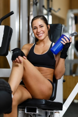 The sports young woman with a protein cocktail in a shaker sits in a gym. Sports nutrition. photo