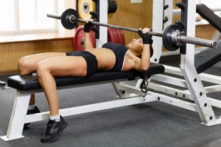 press: Sports young woman doing exercises with barbell on bench in the gym.  Bar Bench Press.