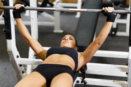 Sport jonge vrouw doen oefeningen met barbell op de bank in de sportschool. Bar Bench Press. Stockfoto