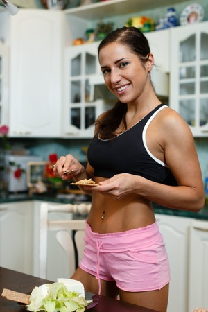 Happy beautiful  woman in sportswear in the house kitchen. Healthy lifestyle. photo