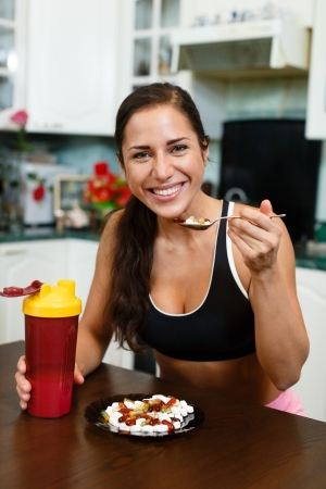 The sports young woman with a protein cocktail in a shaker and plate with nutritional supplements  sits in house kitchen. Sports nutrition.