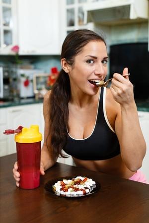 De sportieve jonge vrouw met een eiwit cocktail in een shaker en plaat met voedingssupplementen zit in huis keuken. Sportvoeding.