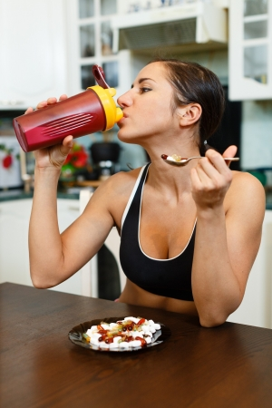 The sports young woman with a protein cocktail in a shaker and plate with nutritional supplements  sits in house kitchen. Sports nutrition. photo