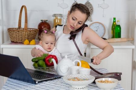madre trabajando: Madre joven con el peque�o ni�o se sienta en la mesa de comedor en la cocina de su casa.