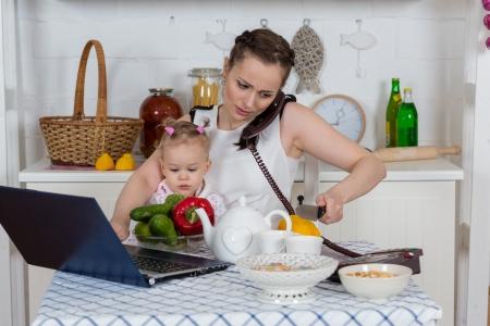 Giovane madre con il piccolo bambino si siede al tavolo da pranzo nella cucina di casa.