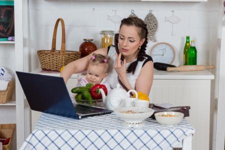 trabajando: Madre joven con el pequeño niño se sienta en la mesa de comedor en la cocina de su casa.