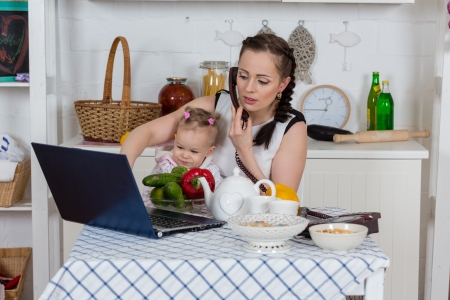 Young mother  with   little child sit at the dining table in the home kitchen. photo