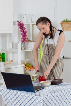 Beautiful woman in an apron with notebook and phone cooks in the kitchen. photo