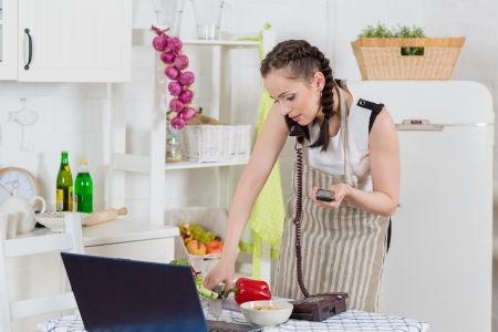 Stressed  young woman in an apron with notebook and phone cooks in the kitchen. photo