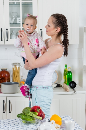 Young mother feeds little daughter  in the home kitchen. Happy family. photo