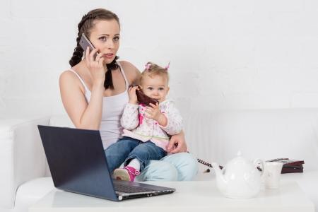 Klein kind en drukke jonge vrouw met laptop en telefoon zitten op de bank in de kamer.
