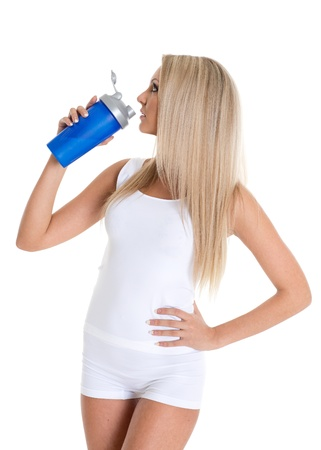 The athletic young beautiful  woman with a protein cocktail in a shaker stands on a white background photo
