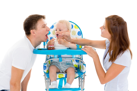 playing with spoon: Young parents feed  baby on a white background