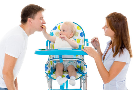 Young parents feed  baby on a white background photo
