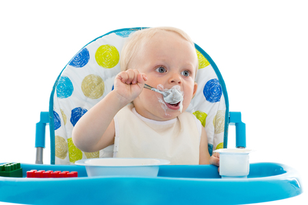 pap: Sweet baby learning to eat with spoon sits on baby chair on a white background.