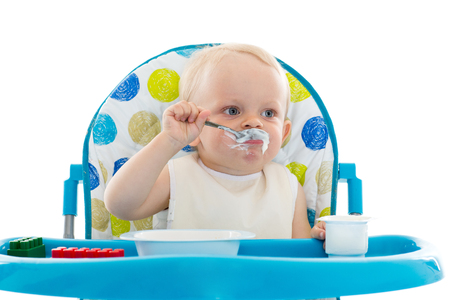 Sweet baby learning to eat with spoon sits on baby chair on a white background. photo